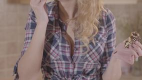 Νέα όμορφη ξανθή γυναίκα πορτρέτου που τρώει λαίμαργα doughnut και που γλείφει τα δάχτυλά της απόθεμα βίντεο