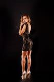 Νέα όμορφη ξανθή γυναίκα στο μαύρο μίνι φόρεμα Στοκ Φωτογραφίες
