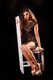 Νέα όμορφη ξανθή γυναίκα στο μαύρο μίνι φόρεμα Στοκ Εικόνες