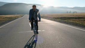 Νέα όμορφη οδήγηση ατόμων στο εκλεκτής ποιότητας ποδήλατο στη εθνική οδό Φίλαθλη ανακύκλωση τύπων στη διαδρομή Αρσενική οδήγηση π φιλμ μικρού μήκους