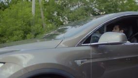 Νέα όμορφη οδήγηση τύπων στο σύγχρονο αυτοκίνητο με τη φίλη του και γέλιο απόθεμα βίντεο