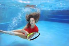 Νέα όμορφη παίζοντας αντισφαίριση κοριτσιών υποβρύχια στην πισίνα Στοκ Εικόνες