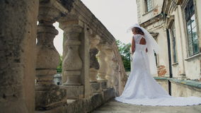 Νέα όμορφη πολυτελής γυναίκα στο γαμήλιο φόρεμα φιλμ μικρού μήκους