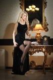 Νέα όμορφη πολυτελής γυναίκα στο μακρύ κομψό μαύρο φόρεμα. Όμορφη νέα ξανθή γυναίκα με τα φωτεινά φω'τα στο υπόβαθρο Στοκ Εικόνα