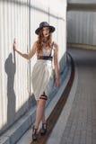 Νέα όμορφη προκλητική γυναίκα που φορά την καθιερώνουσα τη μόδα εξάρτηση, το άσπρο φόρεμα, το μαύρο καπέλο και το δέρμα swordbelt στοκ εικόνες