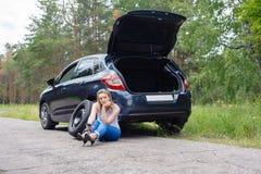 Νέα όμορφη προκλητική γυναίκα στο σπασμένο αυτοκίνητο με το κινητό τηλέφωνο, stan Στοκ Φωτογραφία