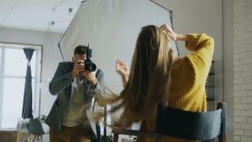 Νέα όμορφη πρότυπη τοποθέτηση γυναικών για τον άνδρα φωτογράφων ενώ πυροβολεί με μια ψηφιακή κάμερα στο στούντιο φωτογραφιών απόθεμα βίντεο