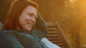 Νέα όμορφη σκεπτόμενη γυναίκα relaxs σε μια γέφυρα-καρέκλα στο πίσω φως ηλιοβασιλέματος που εξετάζει το distanc απόθεμα βίντεο