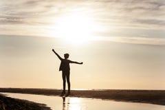 Νέα όμορφη σκιαγραφία κοριτσιών που στέκεται στις ακτίνες του φωτός του ήλιου στον ήλιο Στοκ εικόνες με δικαίωμα ελεύθερης χρήσης