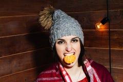 Νέα όμορφη σκοτεινός-μαλλιαρή γυναίκα που χαμογελά στα χειμερινά ενδύματα και την ΚΑΠ με tangerines στο ξύλινο υπόβαθρο Στοκ φωτογραφίες με δικαίωμα ελεύθερης χρήσης