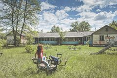 Νέα όμορφη συνεδρίαση γυναικών μέσα στην έλξη στο εγκαταλειμμένο καλοκαιρινό εκπαιδευτικό κάμπινγκ παιδιών Στοκ Φωτογραφίες