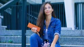 Νέα όμορφη συνεδρίαση γυναικών στα σκαλοπάτια και το πορτοφόλι εκμετάλλευσης υπό εξέταση στοκ εικόνα