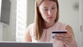 Νέα όμορφη συνεδρίαση γυναικών στο σπίτι Να ψωνίσει on-line με την πιστωτική κάρτα στο lap-top Καταναλωτισμός on-line απόθεμα βίντεο