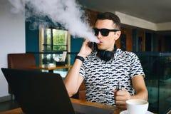 Νέα όμορφη συνεδρίαση ατόμων hipster insunglasse στον καφέ με ένα φλιτζάνι του καφέ, και τις απελευθερώσεις ένα σύννεφο του ατμού Στοκ φωτογραφία με δικαίωμα ελεύθερης χρήσης