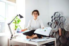 Νέα όμορφη συνεδρίαση επιχειρηματιών στον πίνακα στον εργασιακό χώρο στην αρχή Στοκ Εικόνες