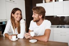 Νέα όμορφη συνεδρίαση ζευγών στο χαμόγελο καφέ πρωινού κατανάλωσης κουζινών στοκ εικόνα με δικαίωμα ελεύθερης χρήσης