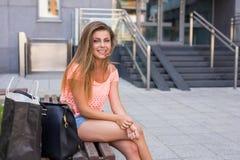 Νέα όμορφη συνεδρίαση κοριτσιών με τον αντίχειρα επάνω ανασκόπηση αστική Στοκ φωτογραφίες με δικαίωμα ελεύθερης χρήσης