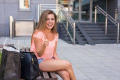 Νέα όμορφη συνεδρίαση κοριτσιών με τον αντίχειρα επάνω ανασκόπηση αστική Στοκ Φωτογραφία
