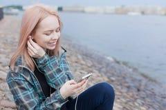 Νέα όμορφη συνεδρίαση κοριτσιών στην παραλία και άκουσμα τη μουσική στο smartphone σας Χαμογελά την απόλαυση της μουσικής Στοκ φωτογραφία με δικαίωμα ελεύθερης χρήσης