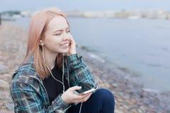 Νέα όμορφη συνεδρίαση κοριτσιών στην παραλία και άκουσμα τη μουσική στο smartphone σας Χαμογελά την απόλαυση της μουσικής Στοκ φωτογραφίες με δικαίωμα ελεύθερης χρήσης