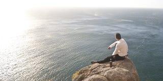 Νέα όμορφη συνεδρίαση τύπων στο βράχο επάνω από τον ωκεανό Στοκ Εικόνα