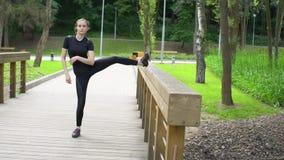 Νέα όμορφη τεντώνοντας κατάρτιση γυναικών στην ξύλινη γέφυρα στο πάρκο στο καλοκαίρι κίνηση αργή απόθεμα βίντεο
