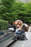 Νέα όμορφη τοποθέτηση γυναικών υπαίθρια με την τσάντα συναυλιών κιθάρων της Στοκ φωτογραφία με δικαίωμα ελεύθερης χρήσης