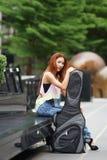 Νέα όμορφη τοποθέτηση γυναικών υπαίθρια με την τσάντα συναυλιών κιθάρων της Στοκ Φωτογραφίες