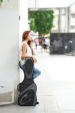 Νέα όμορφη τοποθέτηση γυναικών υπαίθρια με την τσάντα συναυλιών κιθάρων της Στοκ εικόνα με δικαίωμα ελεύθερης χρήσης