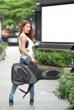 Νέα όμορφη τοποθέτηση γυναικών υπαίθρια με την τσάντα συναυλιών κιθάρων της Στοκ εικόνες με δικαίωμα ελεύθερης χρήσης