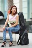 Νέα όμορφη τοποθέτηση γυναικών υπαίθρια με την τσάντα συναυλιών κιθάρων της Στοκ Εικόνα