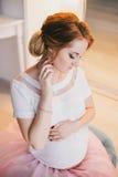 Νέα όμορφη τοποθέτηση εγκύων γυναικών σε ένα εκλεκτής ποιότητας εσωτερικό Στοκ Φωτογραφία