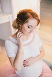 Νέα όμορφη τοποθέτηση εγκύων γυναικών σε ένα εκλεκτής ποιότητας εσωτερικό Στοκ φωτογραφία με δικαίωμα ελεύθερης χρήσης