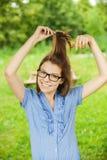 Νέα όμορφη τρίχα χτενών γυαλιών κοριτσιών Στοκ Εικόνα