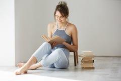 Νέα όμορφη τρυφερή συνεδρίαση βιβλίων ανάγνωσης χαμόγελου κοριτσιών στο πάτωμα πέρα από τον άσπρο τοίχο νωρίς το πρωί Στοκ εικόνα με δικαίωμα ελεύθερης χρήσης