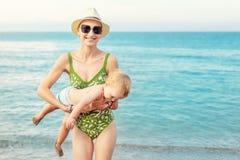 Νέα όμορφη φαλακρή μητέρα που φέρνει το χαριτωμένο καυκάσιο νερό αγοριών μικρών παιδιών σαφές μπλε έξω στην τροπική παραλία τη φω στοκ φωτογραφίες με δικαίωμα ελεύθερης χρήσης