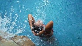 Νέα όμορφη χαλάρωση γυναικών σε μια πισίνα Γυναίκα κάτω από τον καταρράκτη λιμνών κίνηση αργή 1920x1080 απόθεμα βίντεο