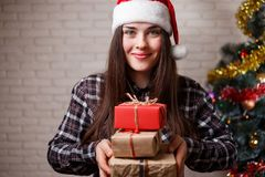 Νέα όμορφη χαμογελώντας γυναίκα σε Santa ΚΑΠ με τα κιβώτια δώρων στο CH Στοκ Φωτογραφίες
