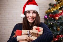 Νέα όμορφη χαμογελώντας γυναίκα σε Santa ΚΑΠ με τα κιβώτια δώρων στο CH Στοκ Εικόνα