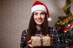 Νέα όμορφη χαμογελώντας γυναίκα σε Santa ΚΑΠ που κρατά ένα δώρο στο chr Στοκ Εικόνα