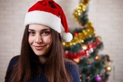Νέα όμορφη χαμογελώντας γυναίκα στο πουλόβερ και Santa ΚΑΠ σε Χριστό Στοκ Εικόνες