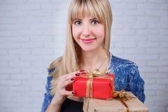 Νέα όμορφη χαμογελώντας ευτυχής γυναίκα με πολλά κιβώτια δώρων υπό εξέταση Στοκ φωτογραφίες με δικαίωμα ελεύθερης χρήσης