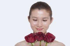 Νέα, όμορφη, χαμογελώντας γυναίκα που εξετάζει κάτω μια δέσμη των κόκκινων τριαντάφυλλων, πυροβολισμός στούντιο Στοκ Φωτογραφία