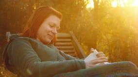 Νέα όμορφη χαμογελώντας γυναίκα relaxs σε μια γέφυρα-καρέκλα που διαβάζει ένα βιβλίο στο πίσω φως ηλιοβασιλέματος απόθεμα βίντεο