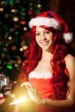 Νέα όμορφη χαμογελώντας γυναίκα santa κοντά στο χριστουγεννιάτικο δέντρο με Στοκ εικόνες με δικαίωμα ελεύθερης χρήσης