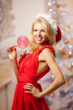 Νέα όμορφη χαμογελώντας γυναίκα santa κοντά στο χριστουγεννιάτικο δέντρο με Στοκ Εικόνες