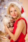 Νέα όμορφη χαμογελώντας γυναίκα santa κοντά στο χριστουγεννιάτικο δέντρο με Στοκ εικόνα με δικαίωμα ελεύθερης χρήσης