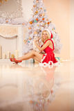 Νέα όμορφη χαμογελώντας γυναίκα santa κοντά στο χριστουγεννιάτικο δέντρο με Στοκ Φωτογραφίες