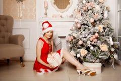 Νέα όμορφη χαμογελώντας γυναίκα santa κοντά στο χριστουγεννιάτικο δέντρο Fas Στοκ Φωτογραφία