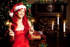 Νέα όμορφη χαμογελώντας γυναίκα santa κοντά στο χριστουγεννιάτικο δέντρο Gir Στοκ Εικόνα